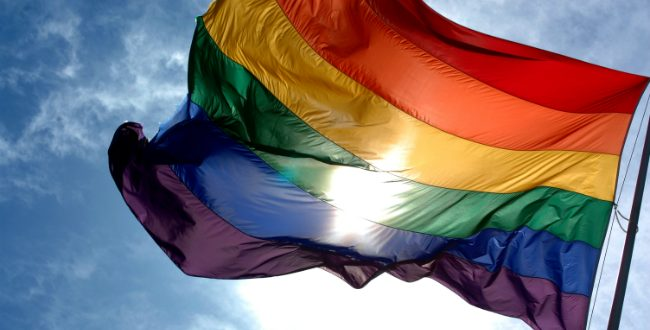 LGBTQ Rainbow Flag waving against a blue sky