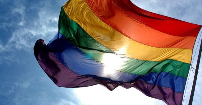 LGBTQ Rainbow Flag waving against a blue sky