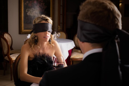 Picture of two people on a date blindfolded.