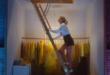 Taylor climbs a ladder to the attic with dresses in background