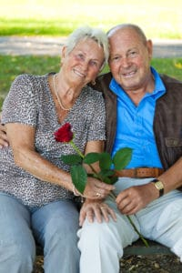 Elderly couple cuddle holding a rose