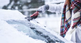 Woman in scarf scraping ice off windshield