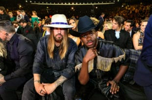 Lil Nas X and Billy Ray Cyrus sitting in the audience at an award show