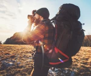 Man hiking and taking pictures with large backpack