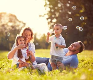 Young family blowing bubbles in field