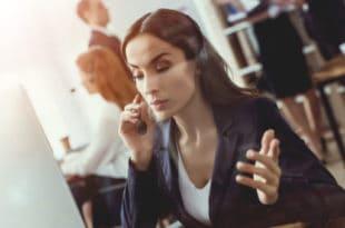 Brunette female call center worker on phone at desk