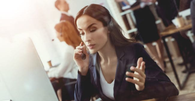 Brunette female call center worker on phone at desk