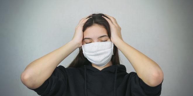 young woman wearing medical facemask holds head in hands