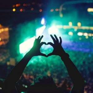 Girl making heart sign at concert