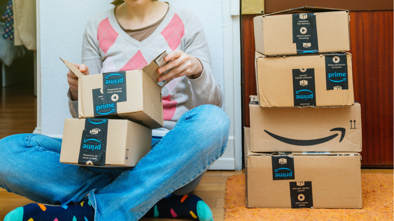 Stack of Amazon Prime packages delivered to a home door woman unboxing one of the small boxes.
