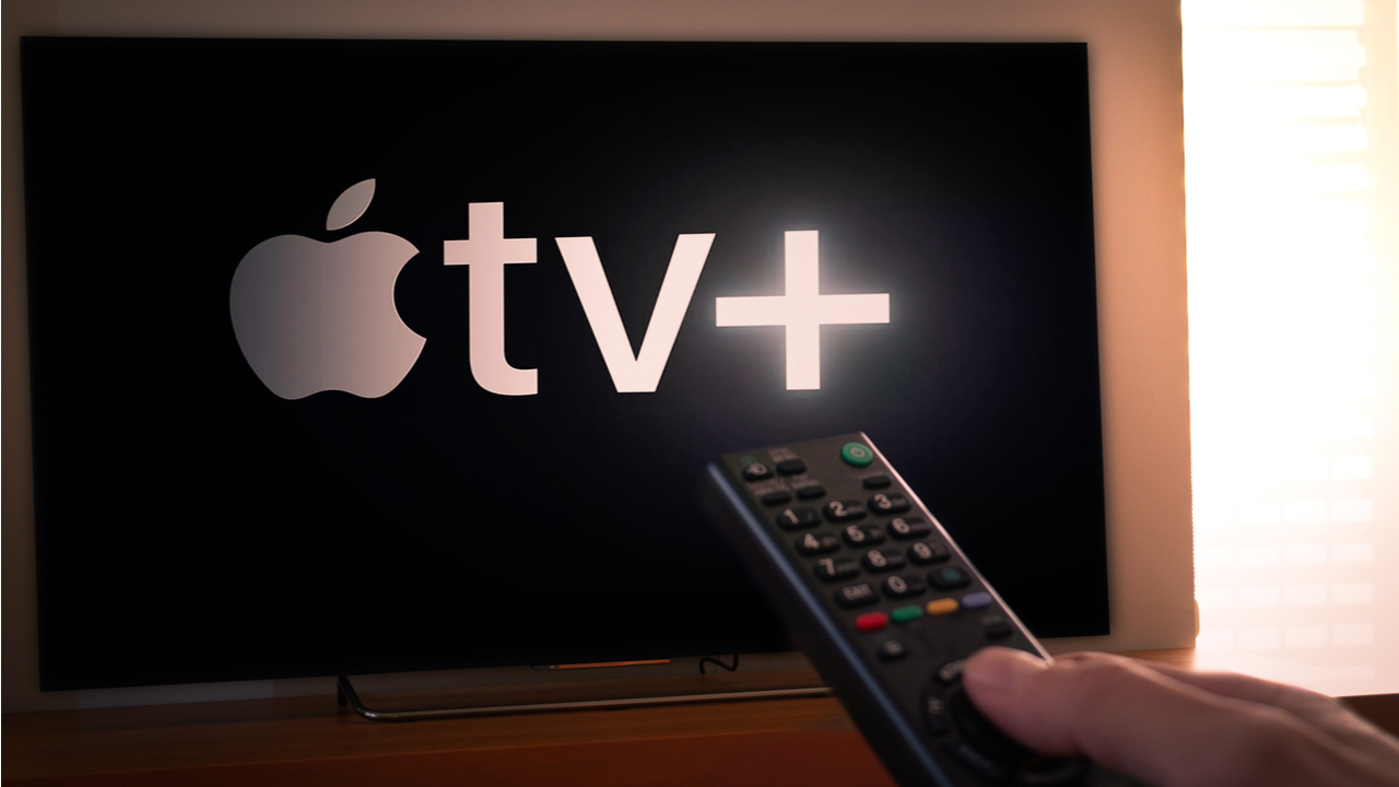 Man holds a remote control With the new Apple TV+ screen on TV.