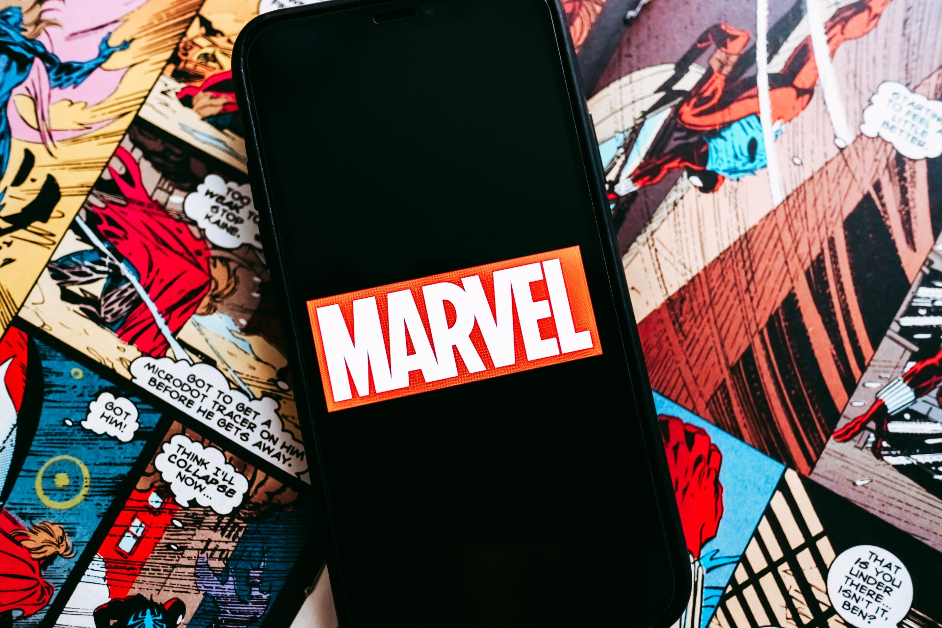 Marvel comics logo on the background of comic pages