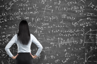 Rear view of a thoughtful woman who tries to solve math problems. Math calculations on black chalk board.