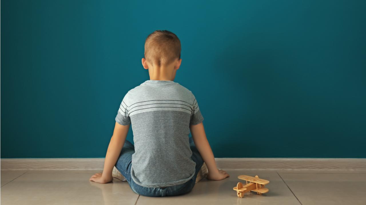 Little boy sitting near dark wall in empty room.