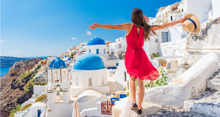 Europe travel vacation fun summer woman dancing in freedom with arms up happy in Oia, Santorini, Greece island. Carefree girl tourist in European destination wearing red fashion dress.