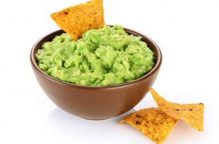 Bowl with guacamole and nachos isolated on white background.