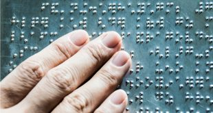 The fingers are touching the metal plate written in the Braille letters;helps the blind to recognize and communicate through the text.