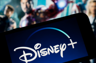 Disney Plus on smartphone screen with the Avengers in the background.
