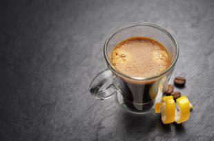 Espresso coffee mug with lemon peel on black background